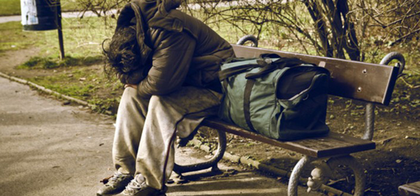 Homeless person doubled over on park bench